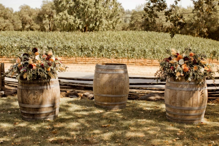 Wine barrels adorned in bouquets of sage greens and orange colored flowers by Julie Stevens Designs for Brie & Tyler at Arista Winery, Healdsburg, by Sharon Burns, Napa Valley Custom Events